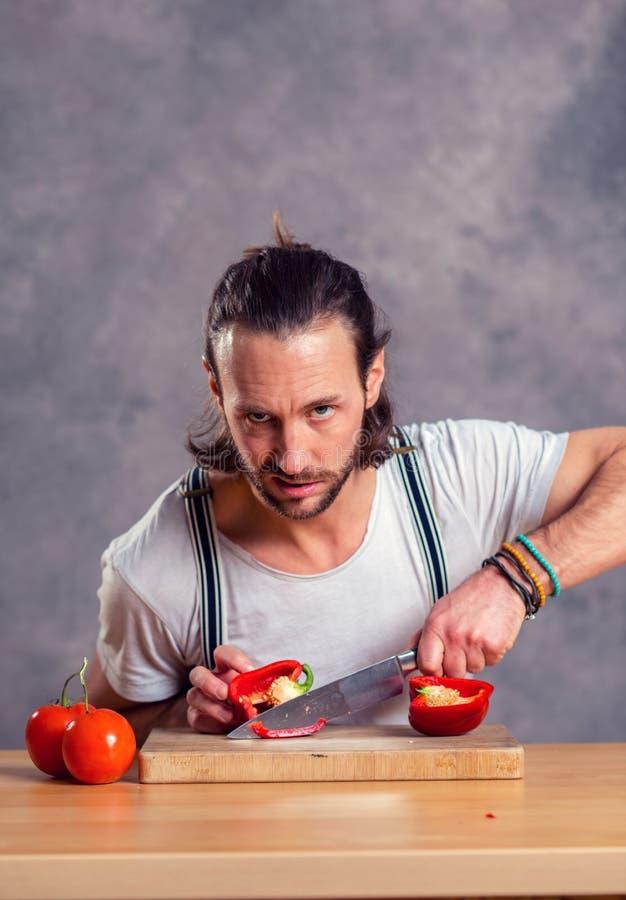 Νέο γενειοφόρο άτομο με το μαγείρεμα του δοχείου στοκ φωτογραφία