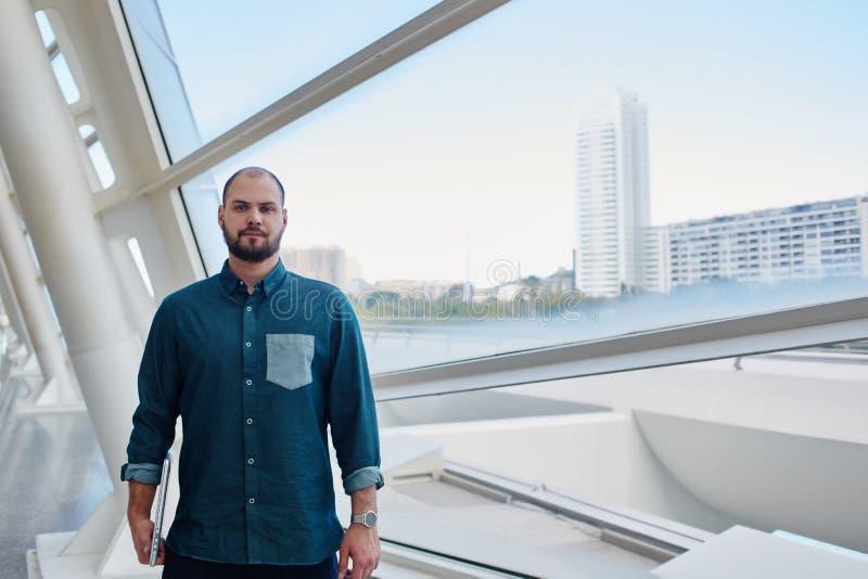 Νέο γενειοφόρο άτομο με το σοβαρό πρόσωπο που στέκεται στο διάδρομο κοντά στο μεγάλο παράθυρο με την άποψη πόλεων στοκ φωτογραφίες με δικαίωμα ελεύθερης χρήσης
