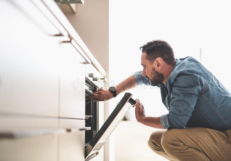Νέο γενειοφόρο άτομο που ελέγχει την ετοιμότητα του πιάτου στο φούρνο στοκ εικόνα