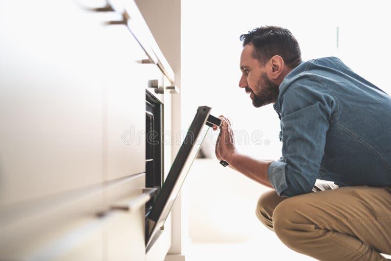 Νέο γενειοφόρο άτομο που ελέγχει το φούρνο στην κουζίνα στοκ φωτογραφία με δικαίωμα ελεύθερης χρήσης