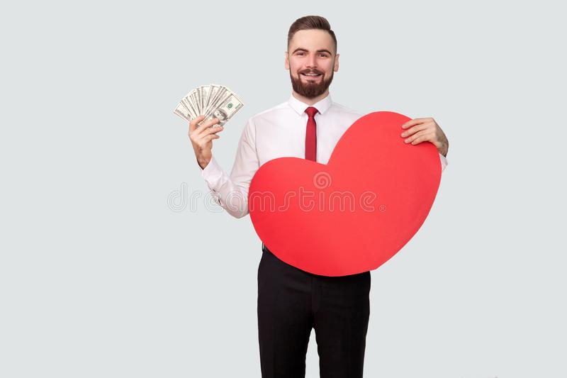 Νέο γενειοφόρο άτομο που κρατά πολλές δολάρια και κόκκινη μορφή καρδιών και που εξετάζει τη κάμερα με το οδοντωτό χαμόγελο στοκ εικόνες