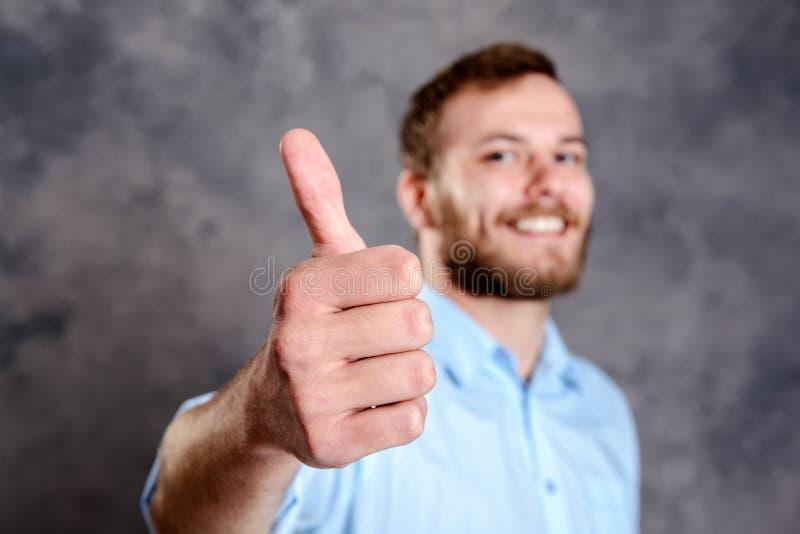Νέο γενειοφόρο άτομο που παρουσιάζει αντίχειρα στοκ φωτογραφία με δικαίωμα ελεύθερης χρήσης