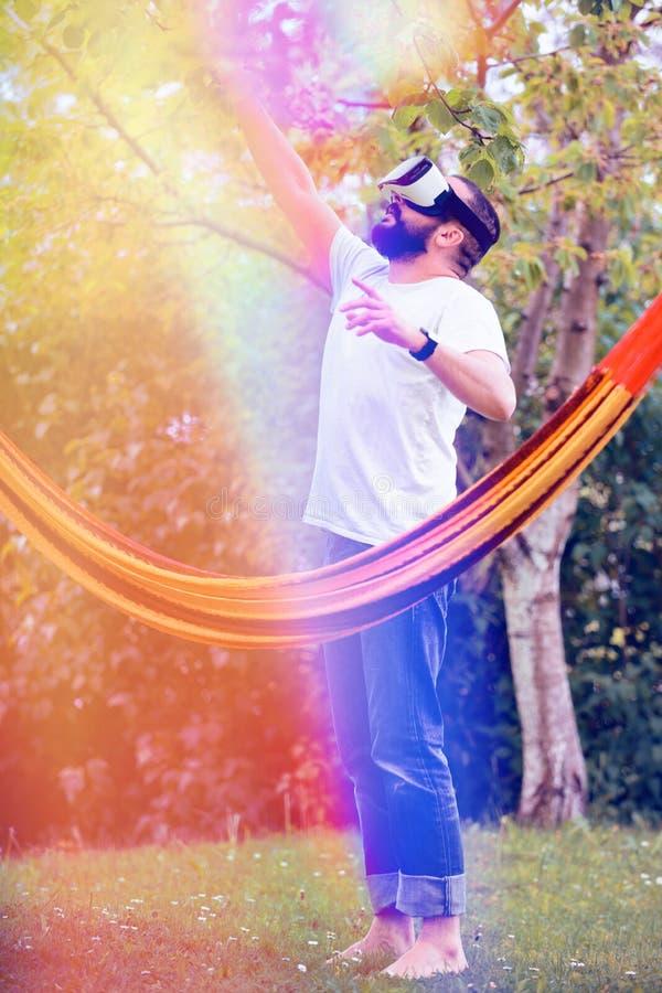 Νέο γενειοφόρο άτομο που φορά τα προστατευτικά δίοπτρα εικονικής πραγματικότητας που έχουν τη διασκέδαση στον κήπο του Η διασκέδα στοκ φωτογραφία
