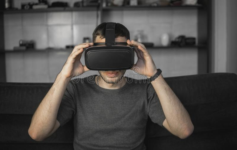 Νέο γενειοφόρο άτομο που φορά την κάσκα της εικονικής πραγματικότητας στη συνεδρίαση γραφείων σε έναν καναπέ στοκ εικόνες