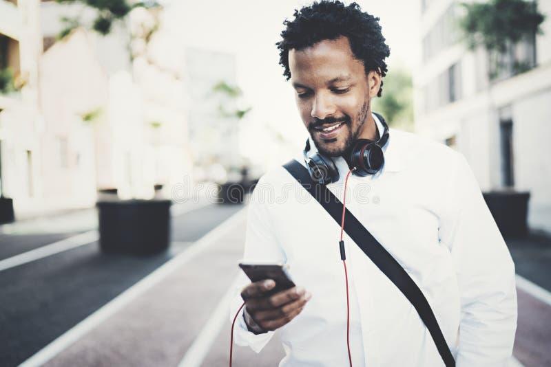 Νέο γενειοφόρο αφρικανικό άτομο που εξετάζει το smartphone στα χέρια περπατώντας στην ηλιόλουστη οδό πόλεων Έννοια της ευτυχούς ε στοκ εικόνες