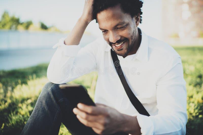 Νέο γενειοφόρο αφρικανικό άτομο που εξετάζει το smartphone στα χέρια καθμένος στο ηλιόλουστο πάρκο πόλεων Έννοια της ευτυχούς επι στοκ φωτογραφία
