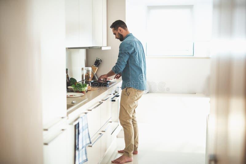 Νέο γενειοφόρο μαγειρεύοντας γεύμα ατόμων στην άνετη κουζίνα στοκ εικόνες