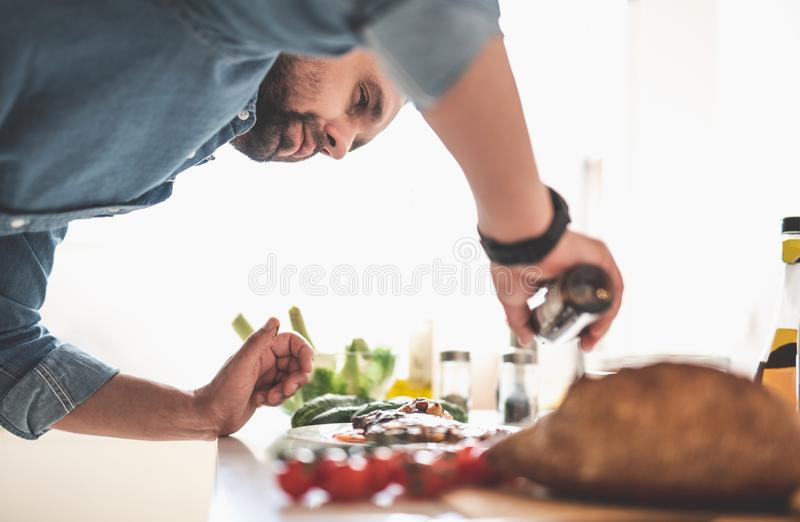 Νέο γενειοφόρο μαγειρεύοντας γεύμα ατόμων στο σπίτι στοκ φωτογραφίες με δικαίωμα ελεύθερης χρήσης