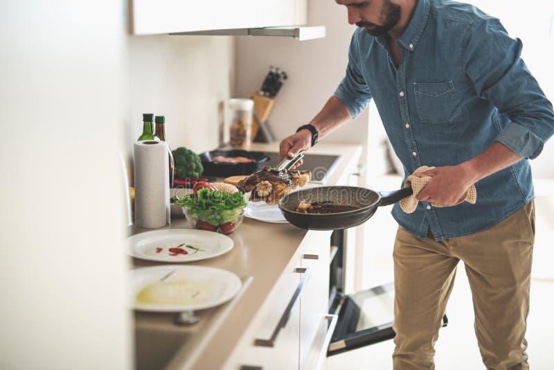 Νέο γενειοφόρο μαγειρεύοντας γεύμα ατόμων στο σπίτι στοκ φωτογραφία με δικαίωμα ελεύθερης χρήσης