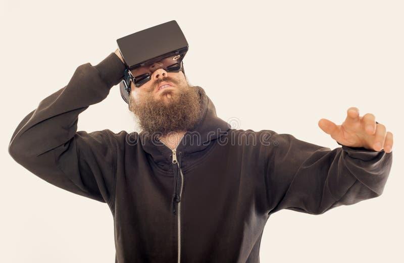 Νέο γενειοφόρο όμορφο άτομο που χρησιμοποιεί τη συσκευή εικονικής πραγματικότητας στοκ φωτογραφία με δικαίωμα ελεύθερης χρήσης