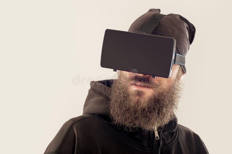 Νέο γενειοφόρο όμορφο άτομο που χρησιμοποιεί τη συσκευή εικονικής πραγματικότητας στοκ εικόνες