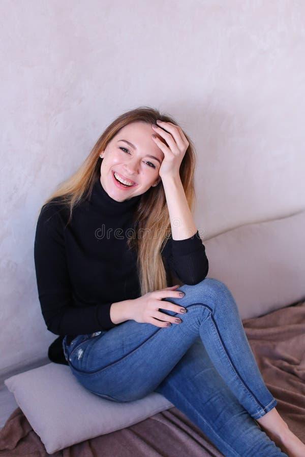 Νέο γοητευτικό κορίτσι που φορά τη μαύρη συνεδρίαση μπλουζών κοντά στον τοίχο στοκ εικόνες