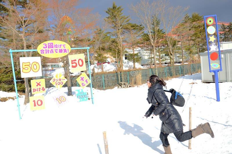 Νέο γυναικείο παίζοντας παιχνίδι στο χιόνι στοκ φωτογραφία