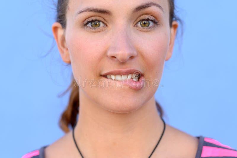 Νέο δάγκωμα γυναικών στα χείλια της στοκ εικόνες