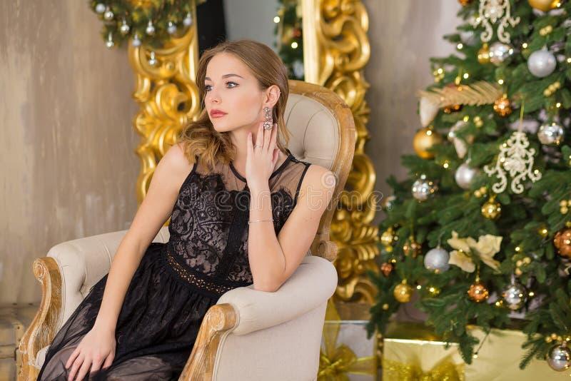 Νέο δέντρο έτους υποβάθρου Χριστουγέννων γυναικών μόδας ομορφιάς Προκλητικό κορίτσι ύφους μόδας Πανέμορφο θηλυκό στο φόρεμα πολυτ στοκ φωτογραφίες