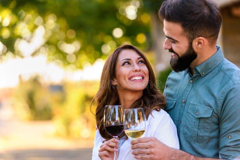 Νέο δοκιμάζοντας κρασί ζευγών χαμόγελου στην οινοποιία υπαίθρια στοκ εικόνες