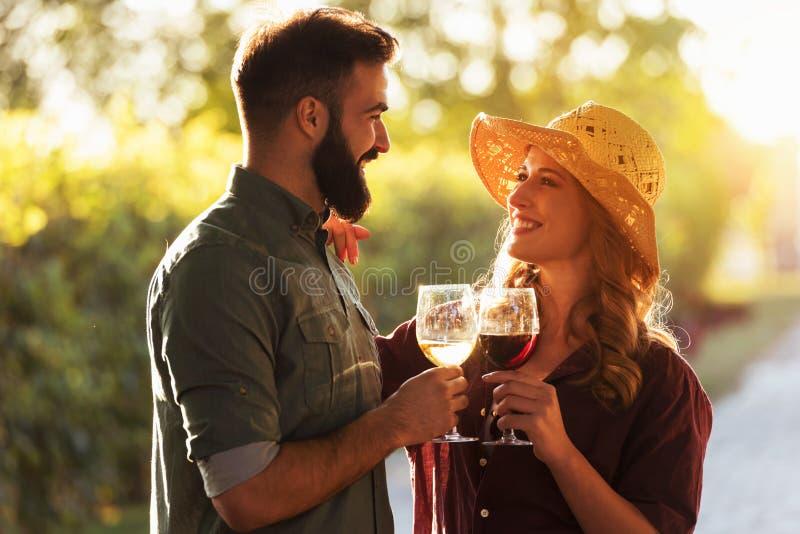 Νέο δοκιμάζοντας κρασί ζευγών χαμόγελου στον αμπελώνα οινοποιιών στοκ φωτογραφίες