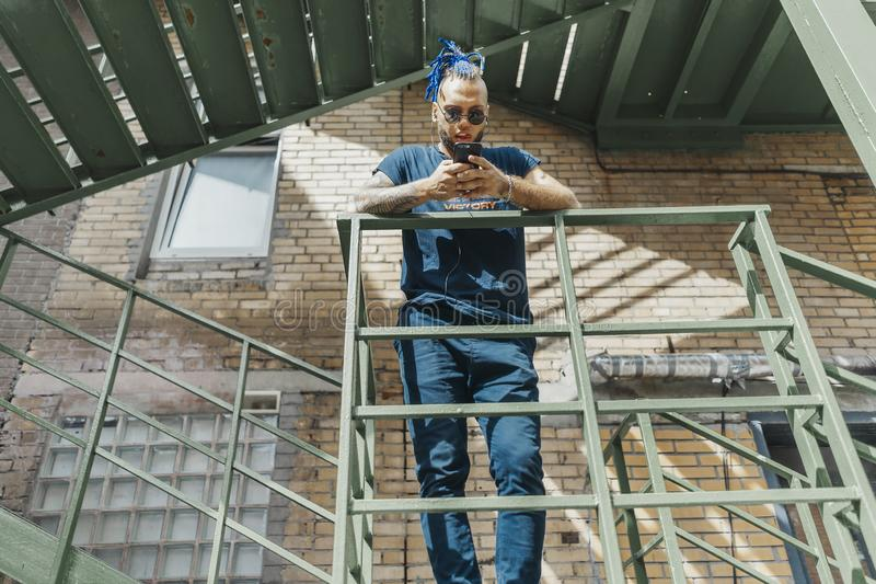 Νέο ελκυστικό άτομο με τα μπλε dreadlocks που στέκονται στη σκάλα στοκ φωτογραφίες