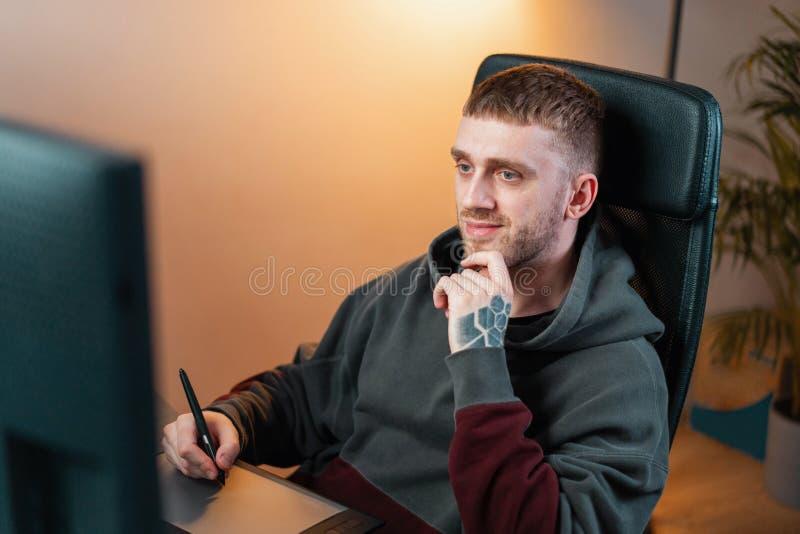 Νέο ελκυστικό άτομο που εργάζεται στην ταμπλέτα γραφικής παράστασης Σύγχρονη θέση εργασίας του σχεδιαστή, ζωγράφος, φωτογράφος στοκ φωτογραφίες με δικαίωμα ελεύθερης χρήσης
