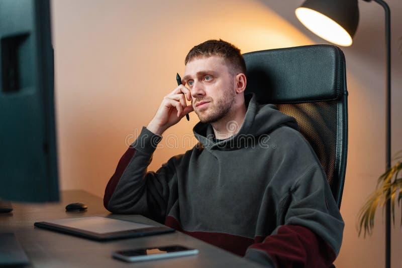 Νέο ελκυστικό άτομο που εργάζεται στην ταμπλέτα γραφικής παράστασης Σύγχρονη θέση εργασίας του σχεδιαστή, ζωγράφος, φωτογράφος στοκ εικόνα