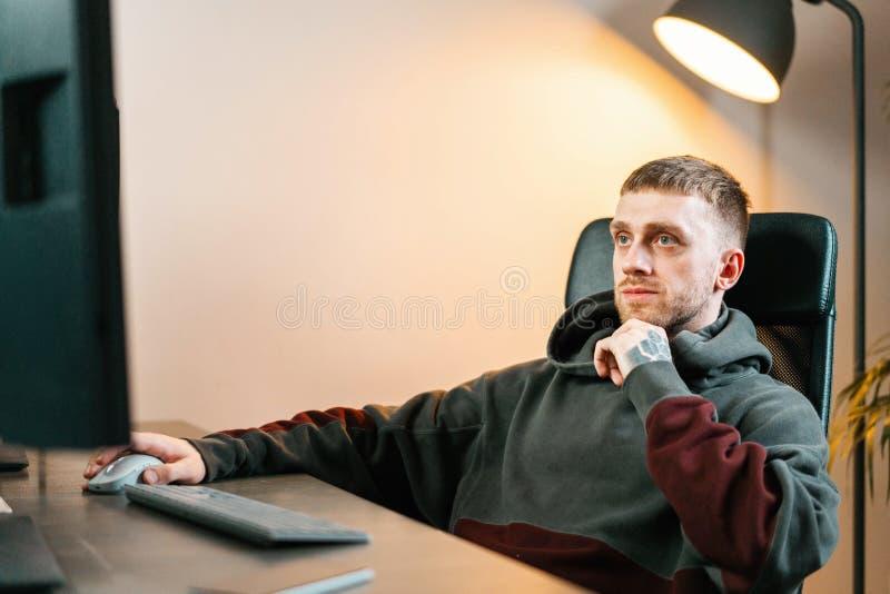 Νέο ελκυστικό άτομο που εργάζεται στο PC Σύγχρονη θέση εργασίας του σχεδιαστή, ζωγράφος, φωτογράφος στοκ φωτογραφίες