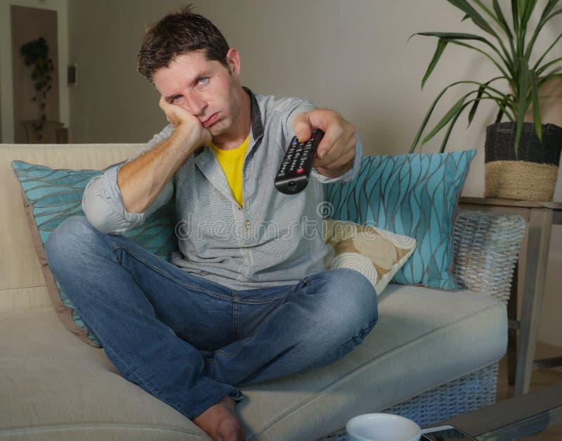 Νέο ελκυστικό δυστυχισμένο άτομο στα περιστασιακά ενδύματα που τρυπιούνται στο σπίτι και στοκ φωτογραφία