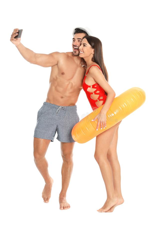 Νέο ελκυστικό ζεύγος σε beachwear με το διογκώσιμο δαχτυλίδι που παίρνει selfie στο λευκό στοκ φωτογραφίες