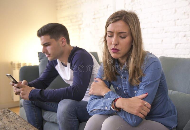 Νέο ελκυστικό ζεύγος στο πρόβλημα σχέσης με τον κινητό φίλο τηλεφωνικού εθισμού Διαδικτύου που αγνοεί λυπημένη παραμελημένη και α στοκ εικόνες