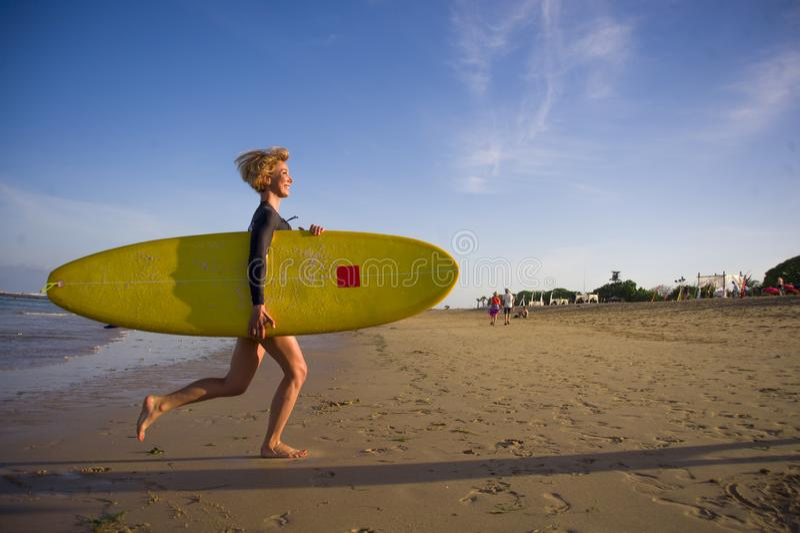 Νέο ελκυστικό και ευτυχές ξανθό κορίτσι surfer στην όμορφη παραλία που φέρνει τον κίτρινο πίνακα κυματωγών που τρέχει έξω της θάλ στοκ φωτογραφίες με δικαίωμα ελεύθερης χρήσης