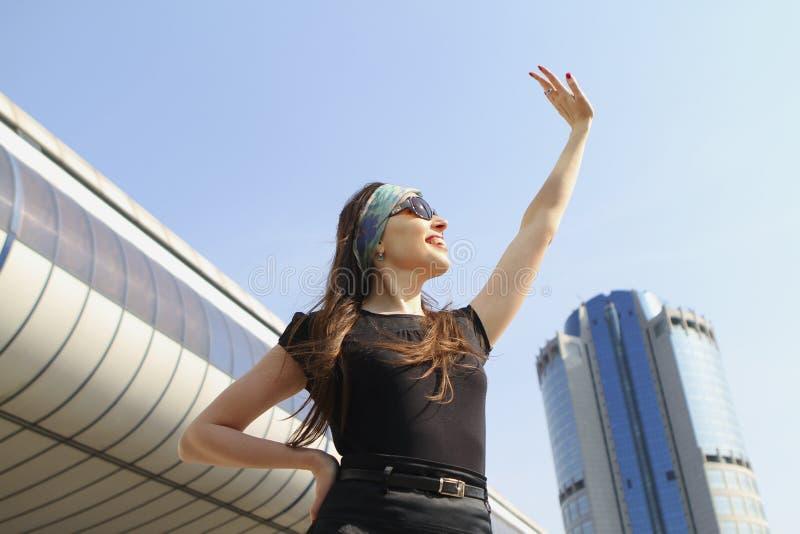 Νέο ελκυστικό κορίτσι που εξετάζει τον ουρανό που κυματίζει το χέρι της ενάντια στοκ εικόνες