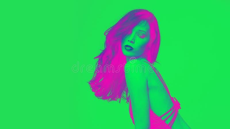 Νέο ελκυστικό κορίτσι στο ζωηρό πυροβολισμό στούντιο χρωμάτων πράσινο και ρόδινο στοκ εικόνες