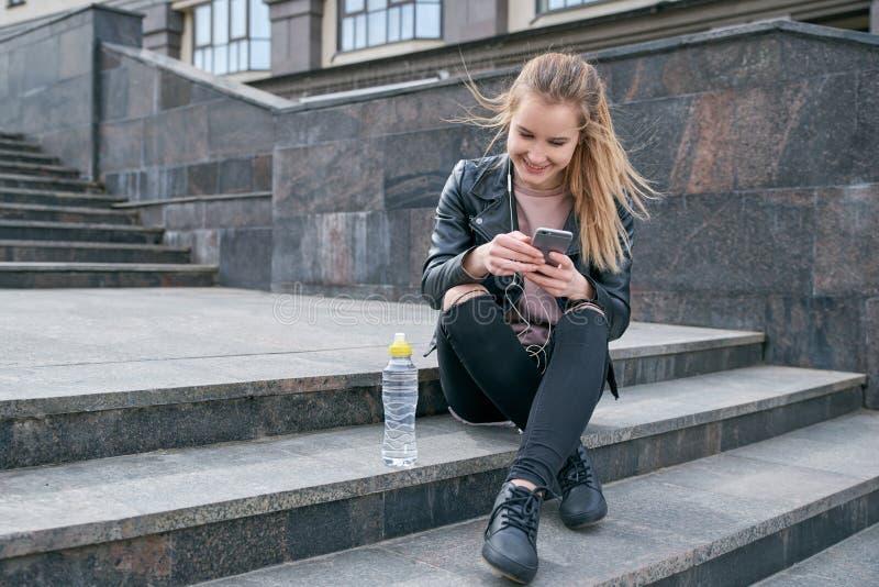 Νέο ελκυστικό χαμογελώντας κορίτσι σε ένα σακάκι και τα τζιν δέρματος που κάθεται στα σκαλοπάτια με ένα smartphone διαθέσιμο στοκ εικόνα