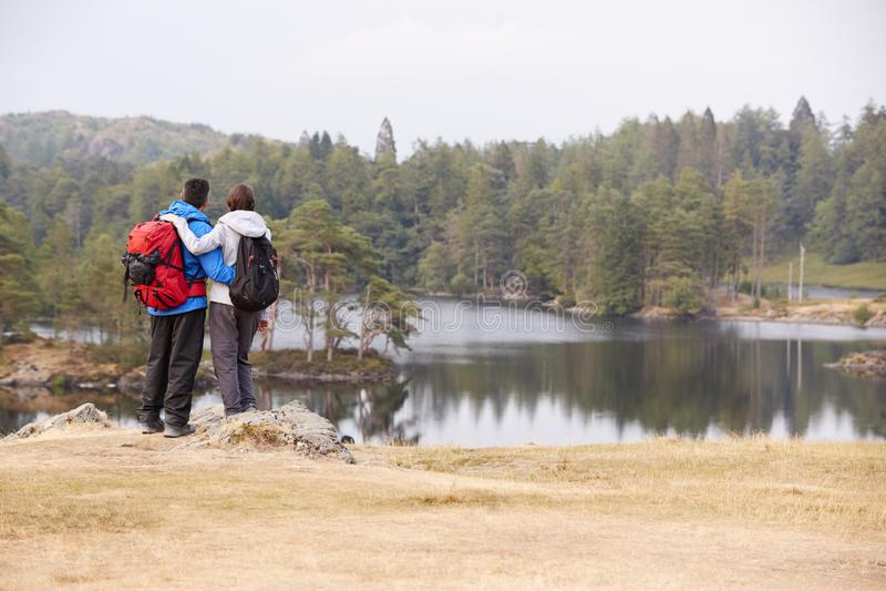 Νέο ενήλικο ζεύγος που στέκεται σε έναν βράχο που θαυμάζει την άποψη όχθεων της λίμνης, πίσω άποψη στοκ εικόνες