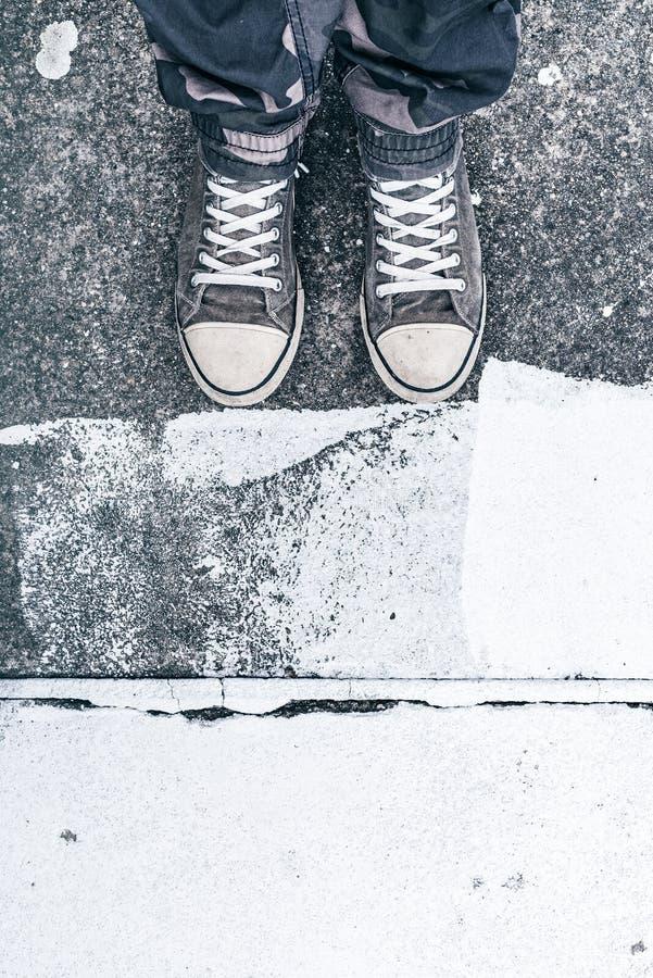 Νέο ενήλικο άτομο που φορά τα πάνινα παπούτσια που στέκονται στην οδό στοκ εικόνες