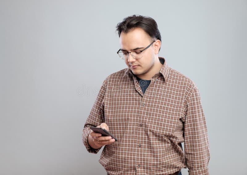 Νέο ενήλικο άτομο που χρησιμοποιεί το κινητό τηλέφωνο στοκ φωτογραφία με δικαίωμα ελεύθερης χρήσης
