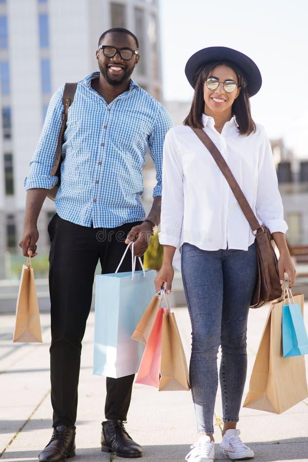 Νέο ενεργό ζεύγος που φαίνεται ικανοποιώ με τις αγορές τους στοκ φωτογραφία με δικαίωμα ελεύθερης χρήσης