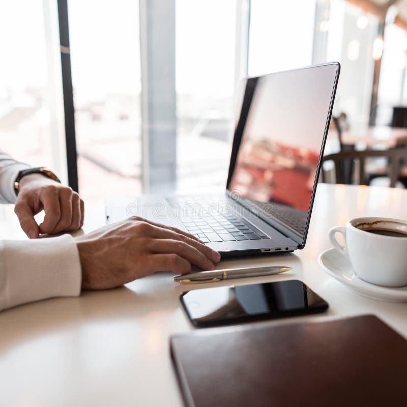 Νέο επαγγελματικό άτομο διευθυντών σε ένα άσπρο πουκάμισο που λειτουργεί στη συνεδρίαση lap-top στον πίνακα στο γραφείο μια ηλιόλ στοκ εικόνες