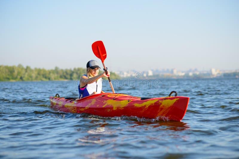 Νέο επαγγελματικό καγιάκ κωπηλασίας Kayaker γυναικών στον ποταμό κάτω από το φωτεινό ήλιο πρωινού Αθλητισμός και ενεργός έννοια τ στοκ εικόνες