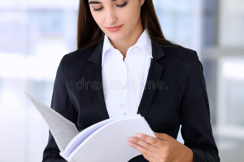 Νέο επιχειρησιακή γυναίκα brunette ή κορίτσι σπουδαστών που εξετάζει το βιβλίο σημειώσεων στοκ εικόνα