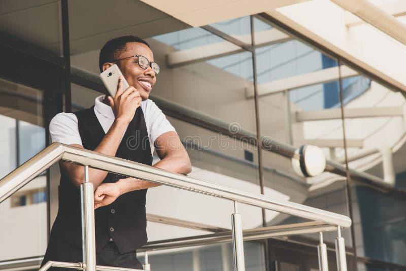Νέο επιχειρησιακό άτομο αφροαμερικάνων στο κοστούμι και eyeglasses που μιλούν στο τηλέφωνο στο υπόβαθρο του εμπορικού κέντρου στοκ φωτογραφία με δικαίωμα ελεύθερης χρήσης