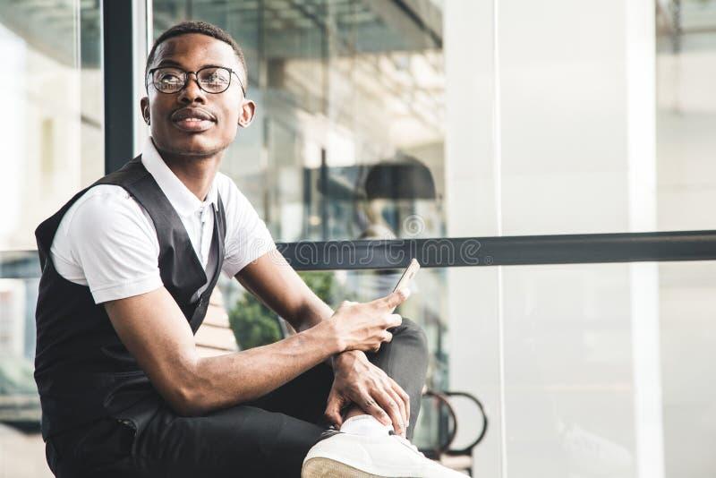 Νέο επιχειρησιακό άτομο αφροαμερικάνων στο κοστούμι και eyeglasses που μιλούν στο τηλέφωνο στο υπόβαθρο του εμπορικού κέντρου στοκ φωτογραφίες με δικαίωμα ελεύθερης χρήσης