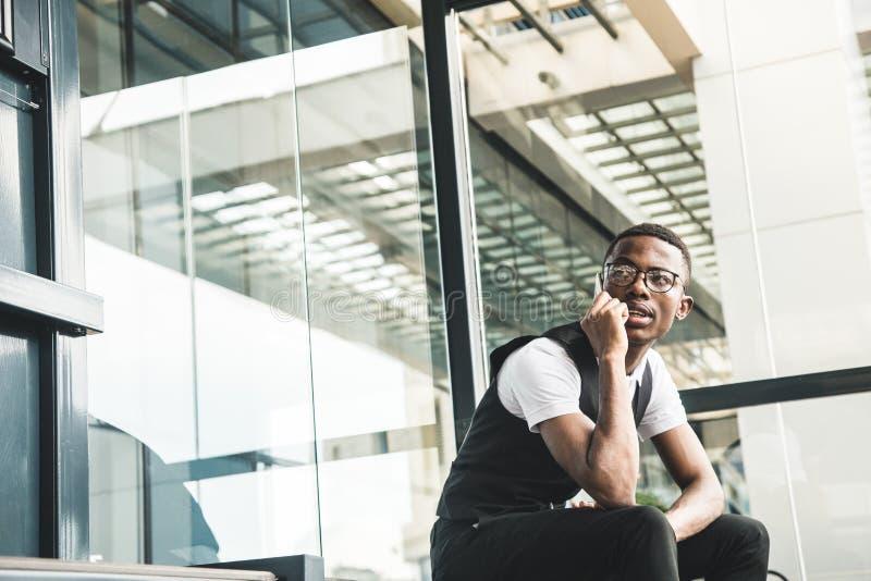 Νέο επιχειρησιακό άτομο αφροαμερικάνων στο κοστούμι και eyeglasses που μιλούν στο τηλέφωνο στο υπόβαθρο του εμπορικού κέντρου στοκ εικόνες