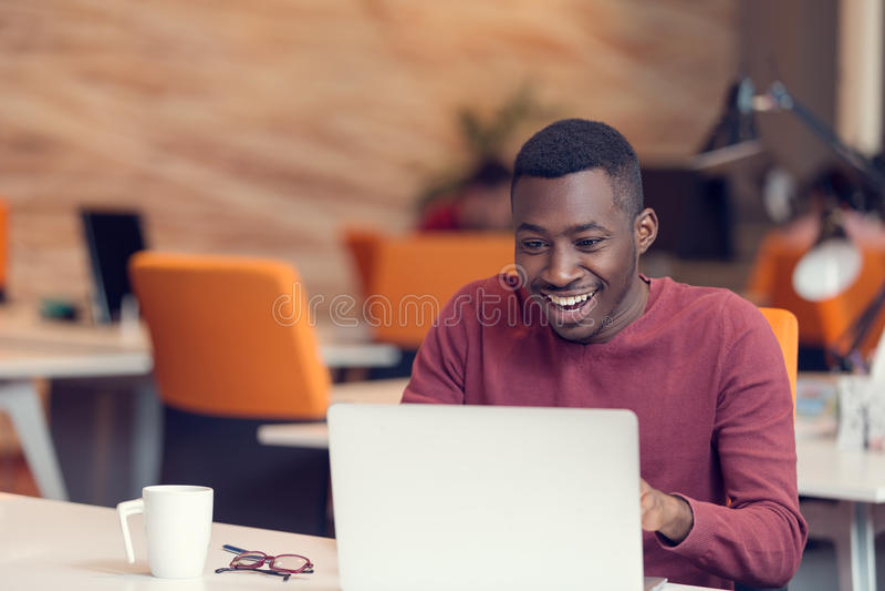 Νέο επιχειρησιακό άτομο με μια συγκλονισμένη έκφραση που λειτουργεί σε ένα lap-top στοκ εικόνες με δικαίωμα ελεύθερης χρήσης