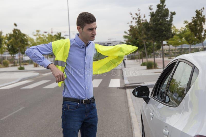 Νέο επιχειρησιακό άτομο που βάζει στην αντανακλαστική φανέλλα έξω από το αυτοκίνητο στοκ εικόνα με δικαίωμα ελεύθερης χρήσης