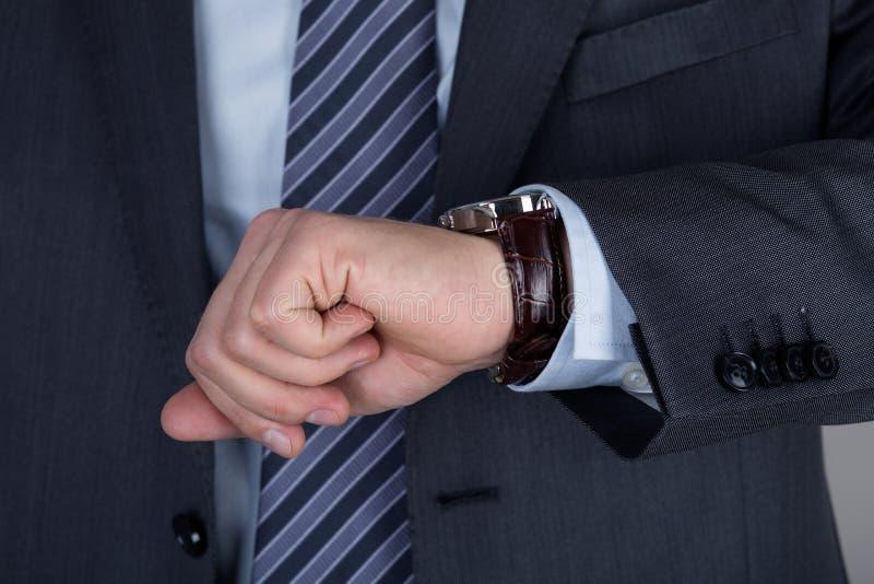Νέο επιχειρησιακό άτομο που εξετάζει το wristwatch του που ελέγχει το χρόνο στοκ φωτογραφία