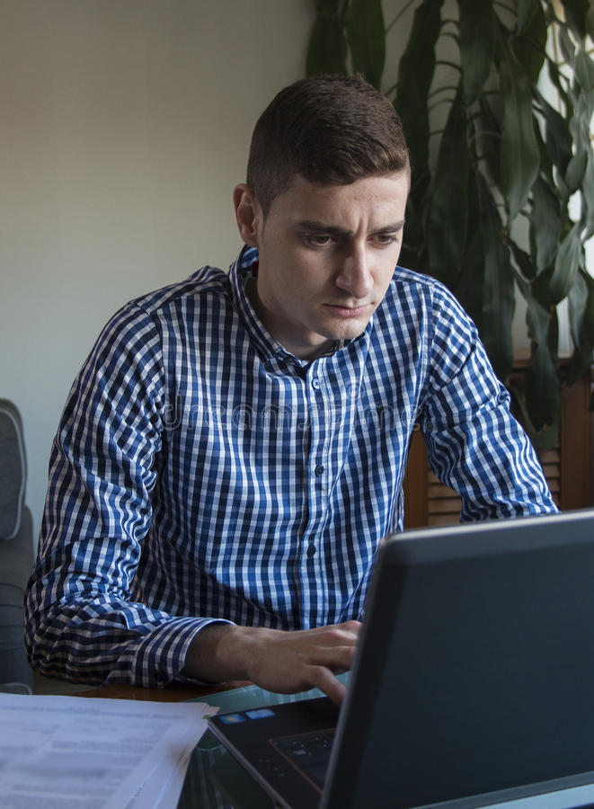 Νέο επιχειρησιακό άτομο που εργάζεται στο γραφείο lap-top του στο σπίτι στοκ εικόνα