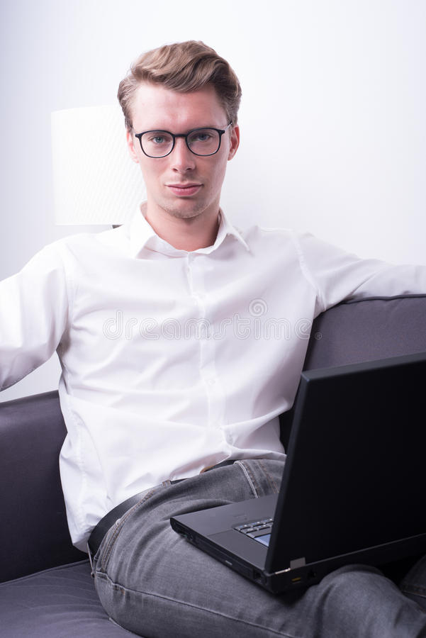 Νέο επιχειρησιακό άτομο που εργάζεται στο σπίτι στον καναπέ στοκ εικόνα με δικαίωμα ελεύθερης χρήσης