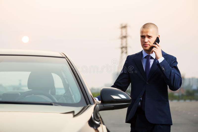 Νέο επιχειρησιακό άτομο που καλεί το τηλέφωνο στο αυτοκίνητο στοκ φωτογραφία με δικαίωμα ελεύθερης χρήσης