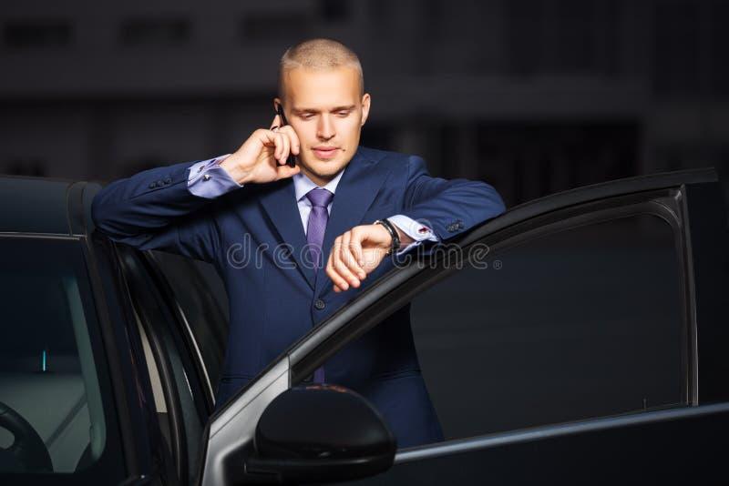 Νέο επιχειρησιακό άτομο που καλεί το τηλέφωνο στο αυτοκίνητο στοκ φωτογραφία