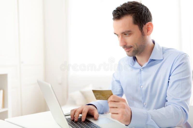 Νέο επιχειρησιακό άτομο που πληρώνει on-line με την πιστωτική κάρτα στοκ φωτογραφία